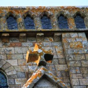 Patina bedeckt Kreuz und Steine hoch oben an der Merveille, dem Wunder des Abendlandes